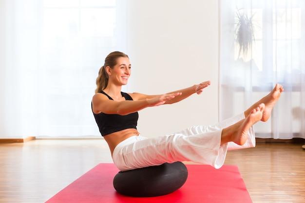 Mulher praticando poses na bola de exercício