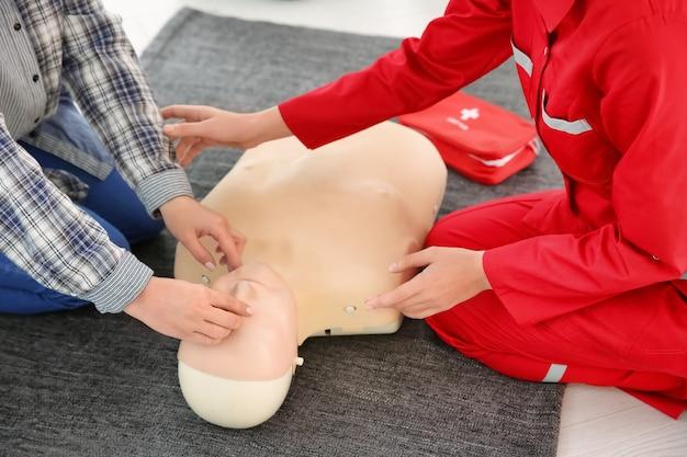 Mulher praticando rcp em manequim na aula de primeiros socorros