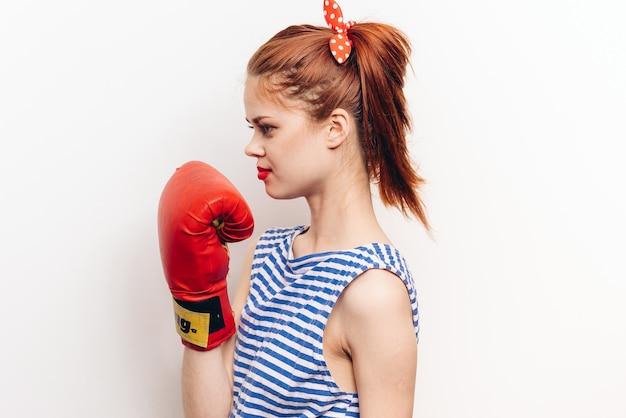 Mulher praticando um golpe com luvas de boxe em um modelo de camiseta listrada de parede clara.