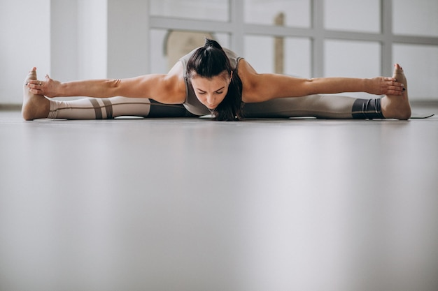 Mulher praticando yoga no ginásio em uma esteira