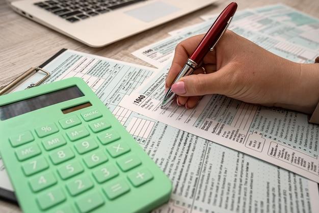 Mulher preenche formulário de imposto individual 1040, conceito de tributação