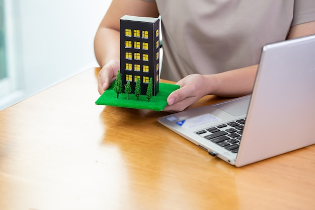 Mulher preenche informações em um computador para enviar um empréstimo de condomínio para o banco