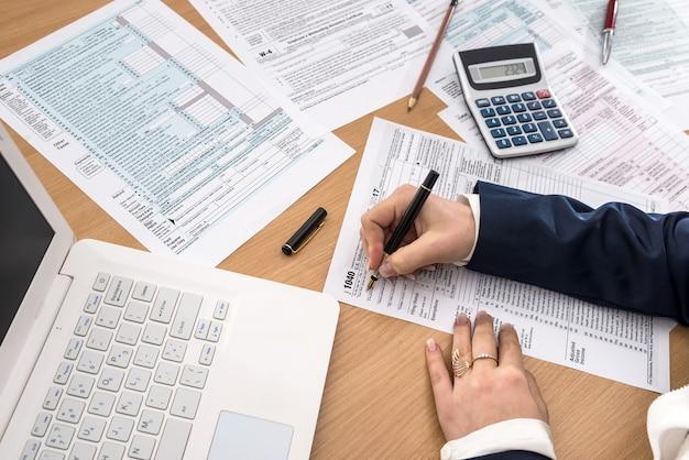 Mulher preenche o formulário fiscal 1040 ao lado do laptop e da calculadora