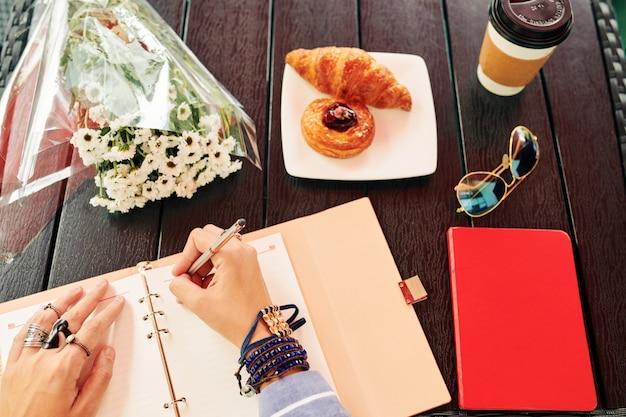 Mulher preenchendo diário de gratidão com pensamentos