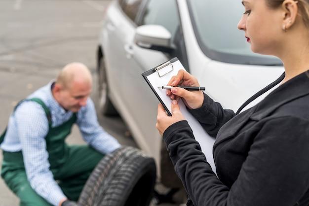 Mulher preenchendo documento enquanto mecânico troca a roda