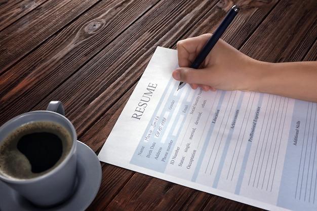 Mulher preenchendo formulário de currículo na mesa de madeira, closeup