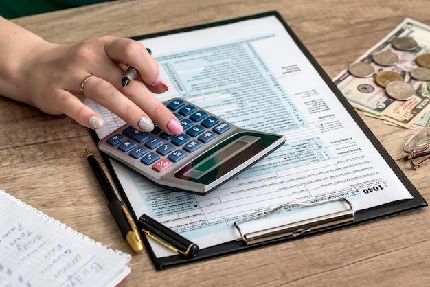 Mulher preenchendo formulário fiscal com dinheiro e calculadora