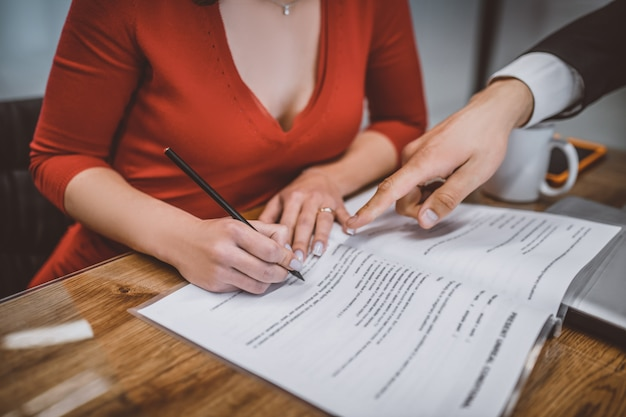 Mulher preenchendo um papel com a ajuda de advogados