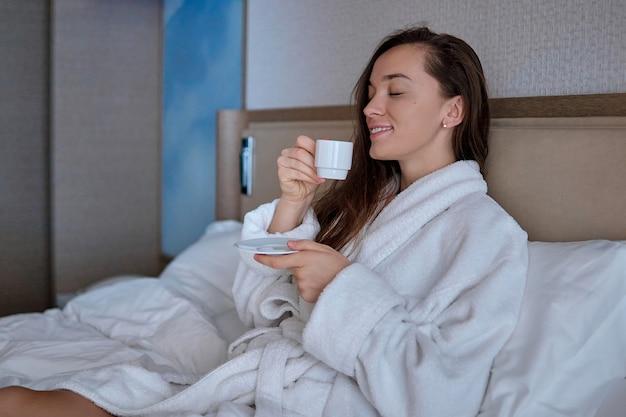 Mulher preguiçosa de roupão deitada na cama desfrutando de bom café da manhã com xícara de café aromático durante relaxamento em aconchegante quarto confortável em quarto de hotel