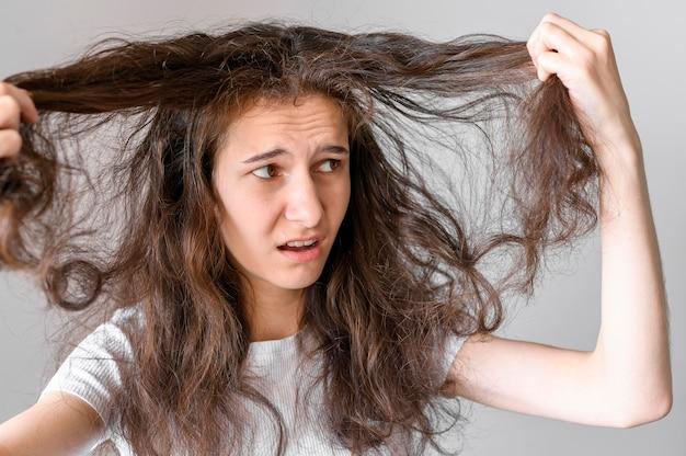 Mulher preocupada com cabelos emaranhados