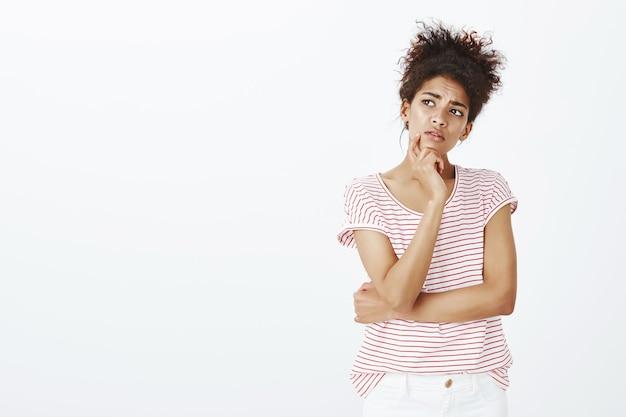 Mulher preocupada com o foco e penteado afro posando no estúdio