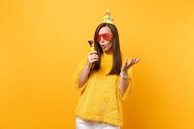 Mulher preocupada em óculos engraçados laranja, chapéu de aniversário, olhando jogando cachimbo, espalhando as mãos, comemorando isolado em fundo amarelo. emoções sinceras de pessoas, conceito de estilo de vida. área de publicidade.