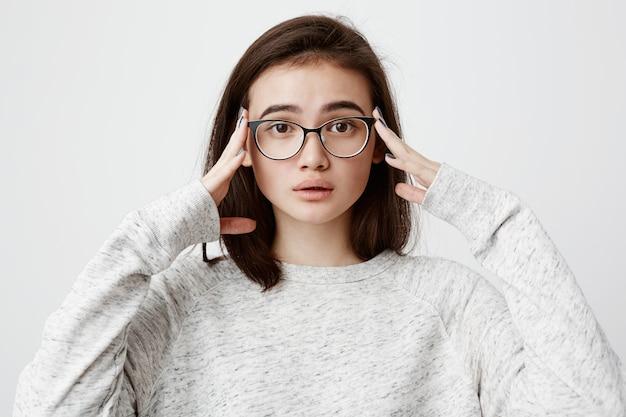Mulher preocupada emocional com cabelos escuros, usando óculos, segurando as mãos na cabeça, sentindo-se perplexa e frustrada depois que saiu de casa sem ter o ferro desconectado. emoções e sentimentos humanos