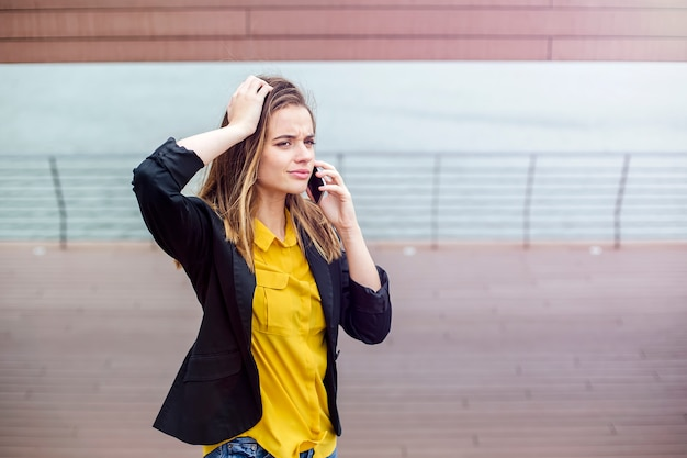 Mulher preocupada fala ao telefone andando na rua