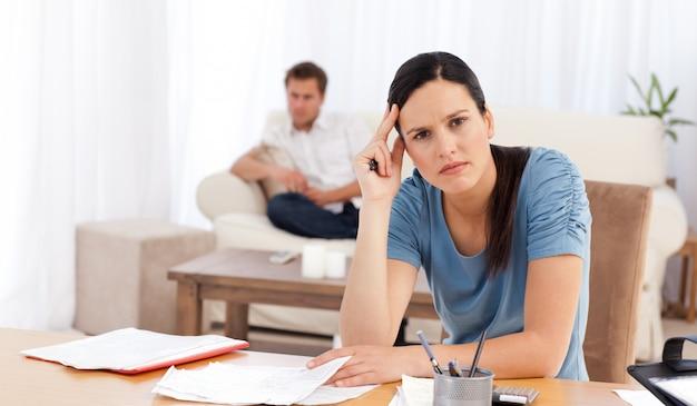Mulher preocupada fazendo sua conta enquanto seu namorado esperando na sala de estar