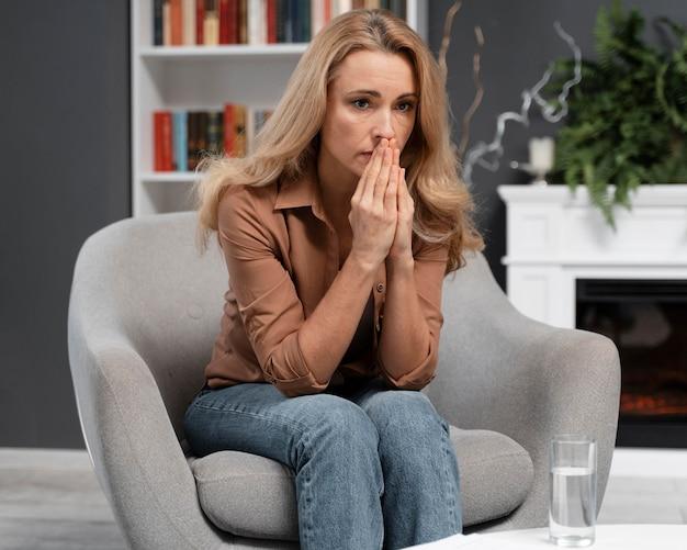 Mulher preocupada no meio do tiro no consultório do terapeuta