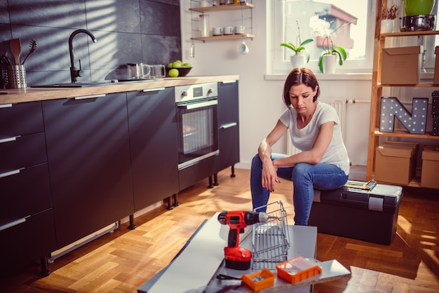 Mulher preocupada, reformando a cozinha