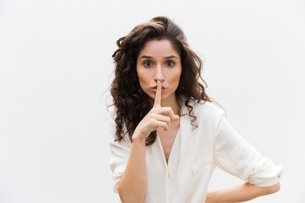 Mulher preocupada séria mostrando shh gesto