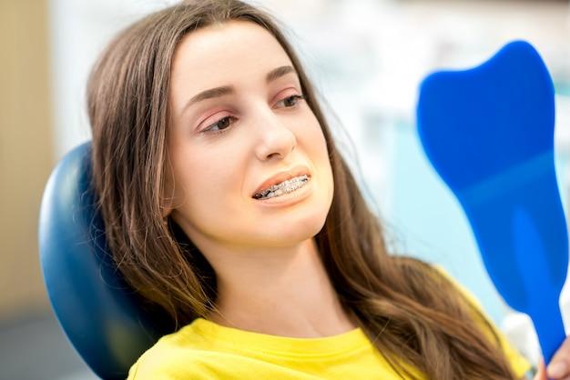 Mulher preocupada sorrindo com aparelho ortodôntico olhando no espelho do consultório odontológico