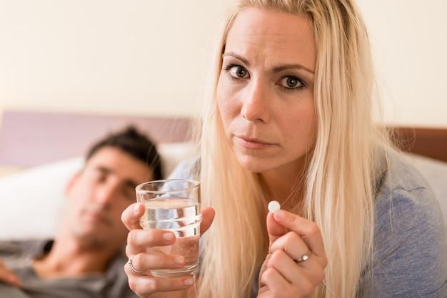Mulher preocupada tomar uma pílula antes de dormir à noite
