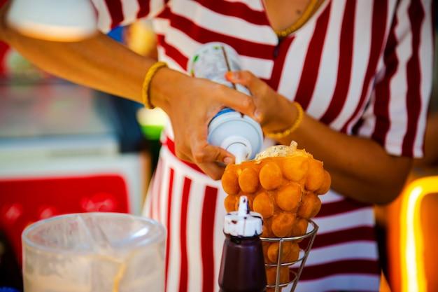Mulher prepara duas sobremesas, sorvete com banana e biscoitos na mesa waffle de hong kong com creme