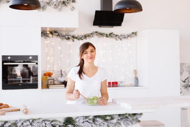 Mulher prepara salada em casa na cozinha