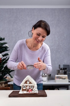 Mulher preparando a casa do pão de mel. quadro vertical.