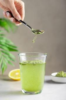 Mulher preparando bebida com pó de superalimento verde. suporte de imunidade.
