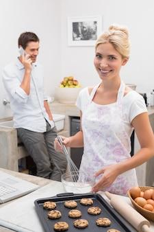 Mulher preparando biscoitos enquanto o homem de plantão na cozinha