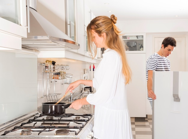 Mulher preparando comida enquanto o marido olhando na geladeira