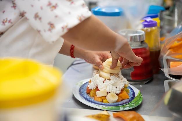 Mulher preparando coquetel de frutas em mercado popular no méxico
