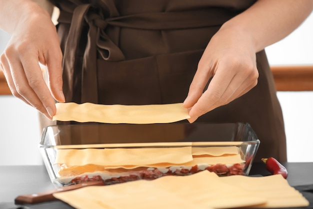 Mulher preparando lasanha de carne na cozinha, closeup