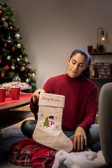 Mulher preparando meias gigantes para o papai noel para deixar presentes