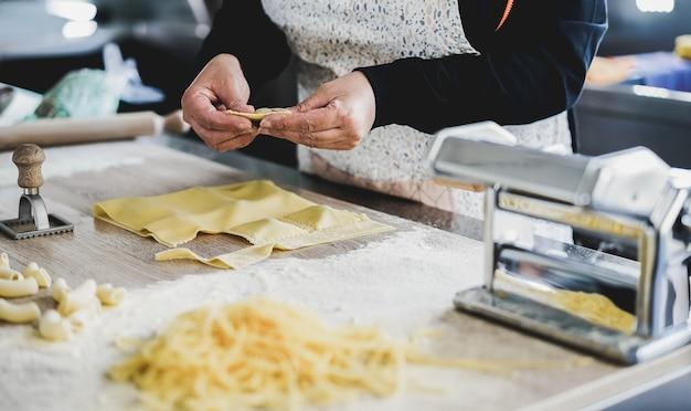 Mulher preparando ravióli fresco dentro da fábrica de macarrão - foco nas mãos