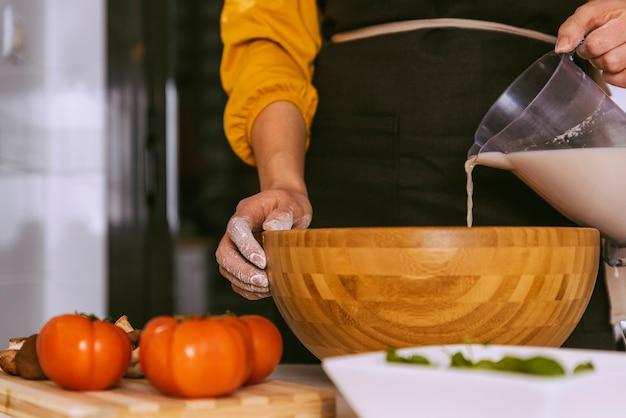Mulher preparando uma deliciosa pizza com ingredientes saudáveis. conceito feito em casa.