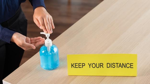 Mulher pressionando álcool gel desinfetante para as mãos para a prevenção de surtos coronavírus