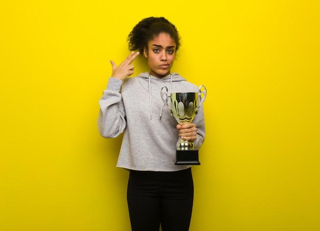 Mulher preta da aptidão nova que faz um gesto do suicídio. segurando um troféu.