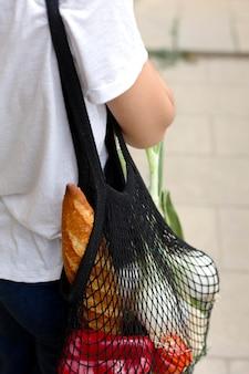 Mulher processando uma sacola sustentável para comprar mantimentos