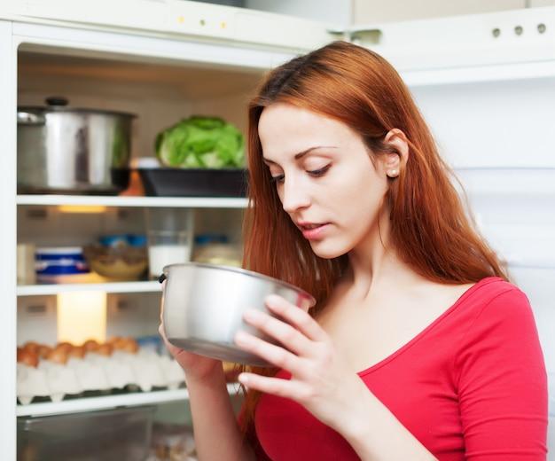 Mulher procura algo na panela perto do frigorífico
