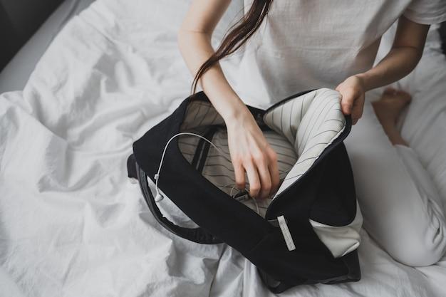 Mulher procurando algo em uma mochila