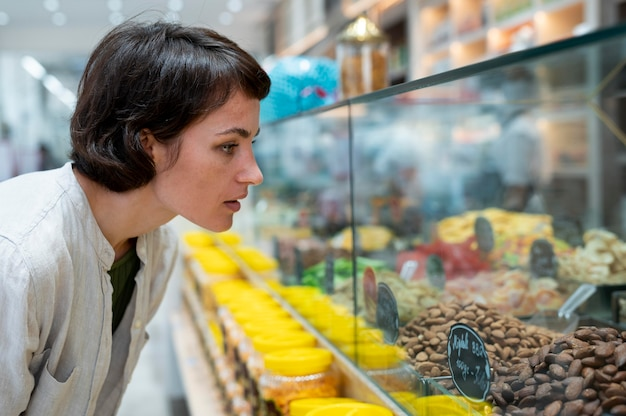 Mulher procurando guloseimas diferentes em um produtor local