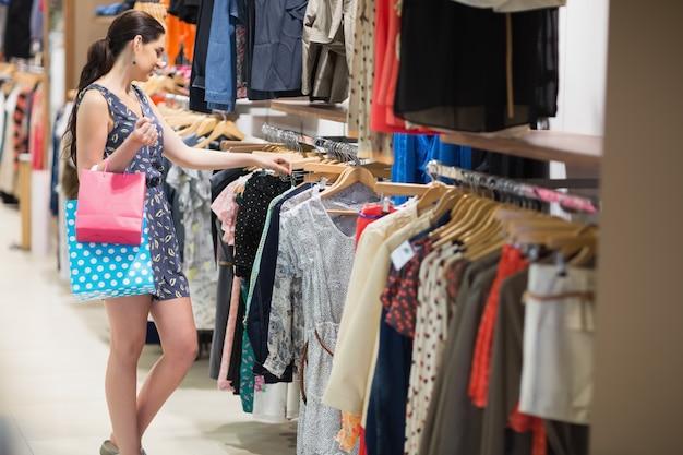 Mulher procurando roupas com dois sacos