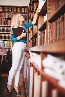 Mulher procurando um livro na biblioteca