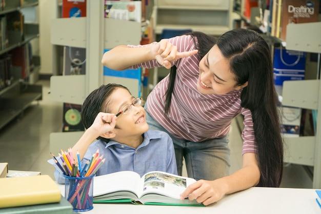 Mulher professora e garoto estudante aprender com o livro no fundo da estante
