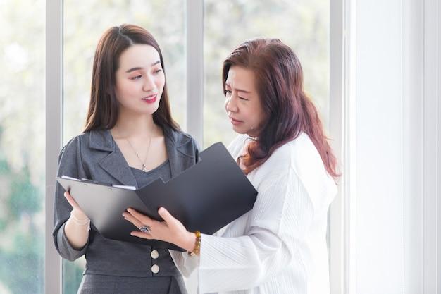 Mulher profissional asiática fala com seu chefe para consultar sobre o trabalho em um documento de arquivo em suas mãos no local de trabalho.