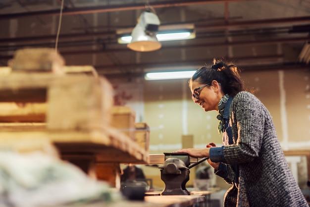 Mulher profissional bonita da idade média do carpinteiro que trabalha com torno de aço em uma tabela na oficina.