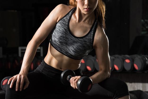 Mulher profissional da aptidão do esporte, peso de levantamento da mulher asiática no fitness center.