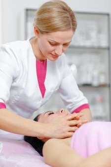 Mulher profissional massageando o rosto do cliente