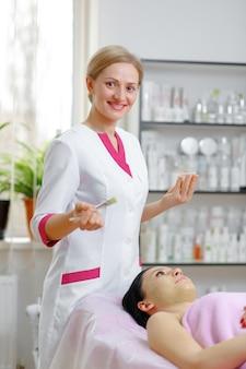 Mulher profissional que aplica o creme verde com uma escova e sorrindo