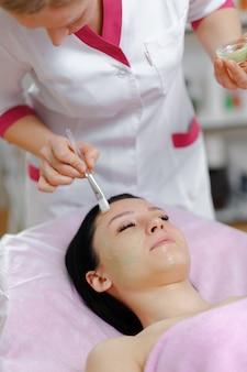 Mulher profissional que aplica o creme verde com uma escova